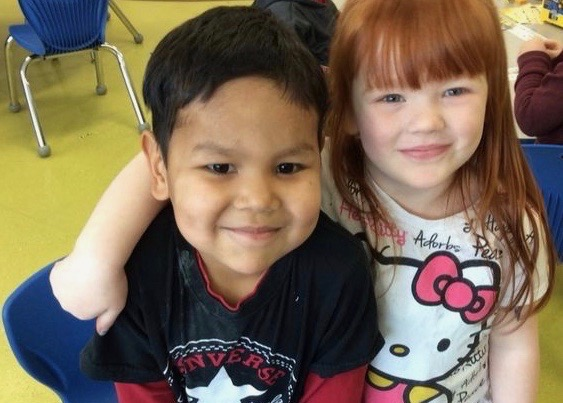 Two Kindergarten students stand smiling.