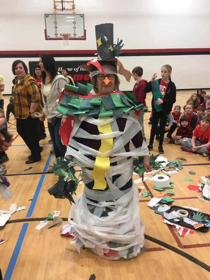 A giant crafted snowman stands in the centre of the school gym, with student and staff surrounding it and laughing.