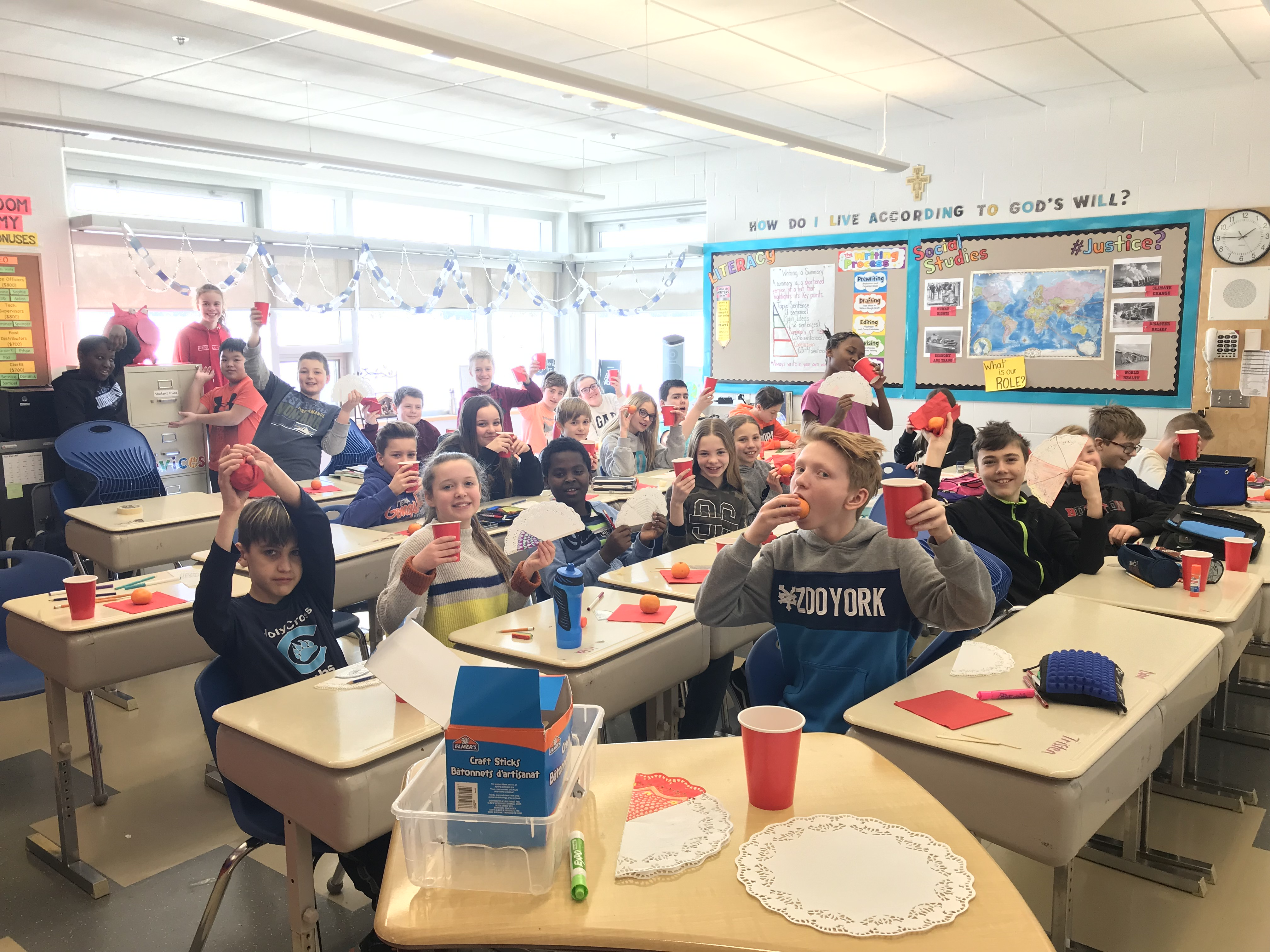 Grade 6 students at Holy Cross School raise their hands in celebration of Chinese New Year!