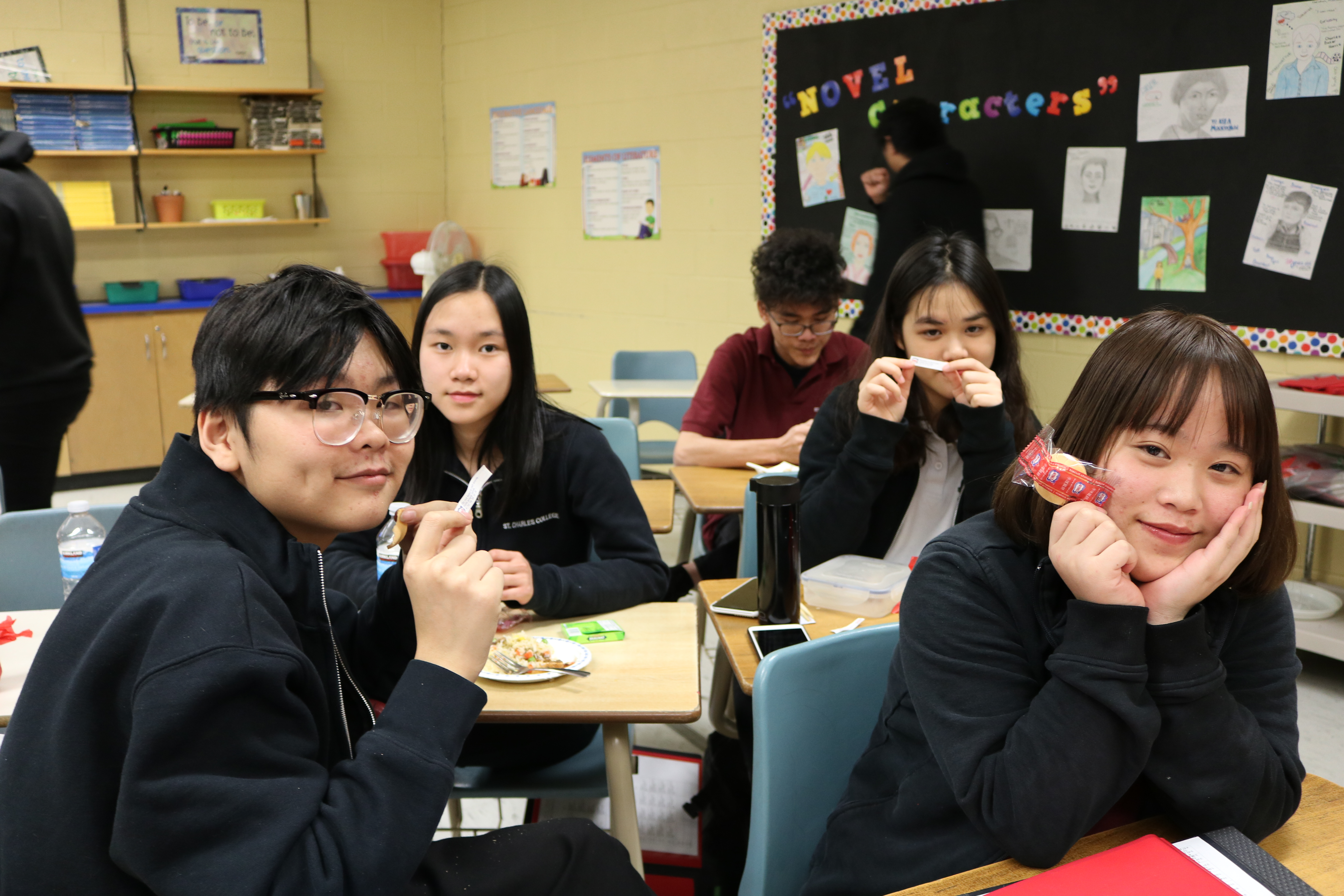 Chinese Students sit smiling as they feast on a traditional Chinese meal.