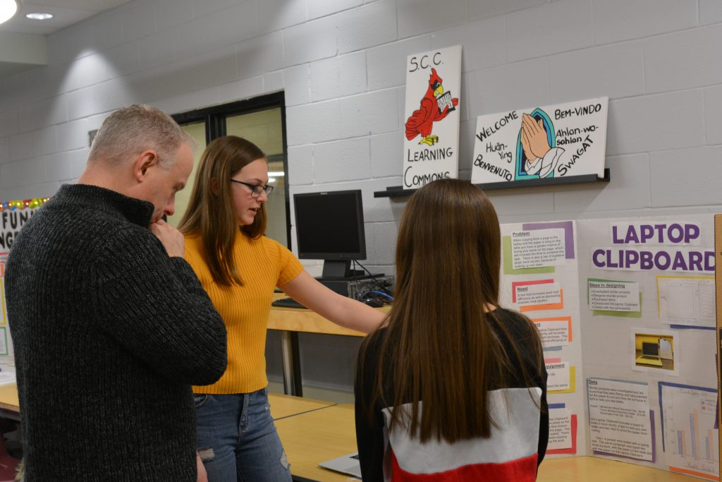 A judge asks two female students questions about their project.