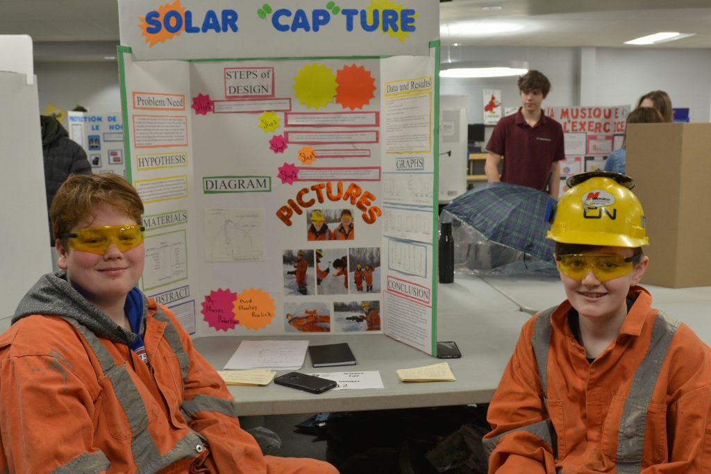 Two male students are dressed in mining gear as they show off their project on solar capture.