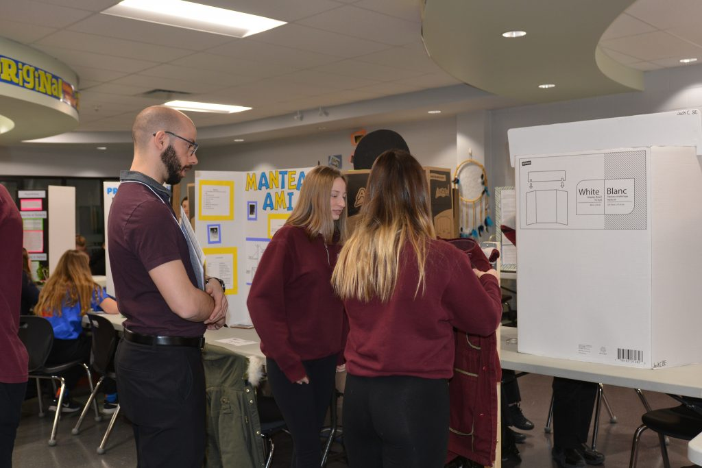A judge watches as two female students demonstrate their project.