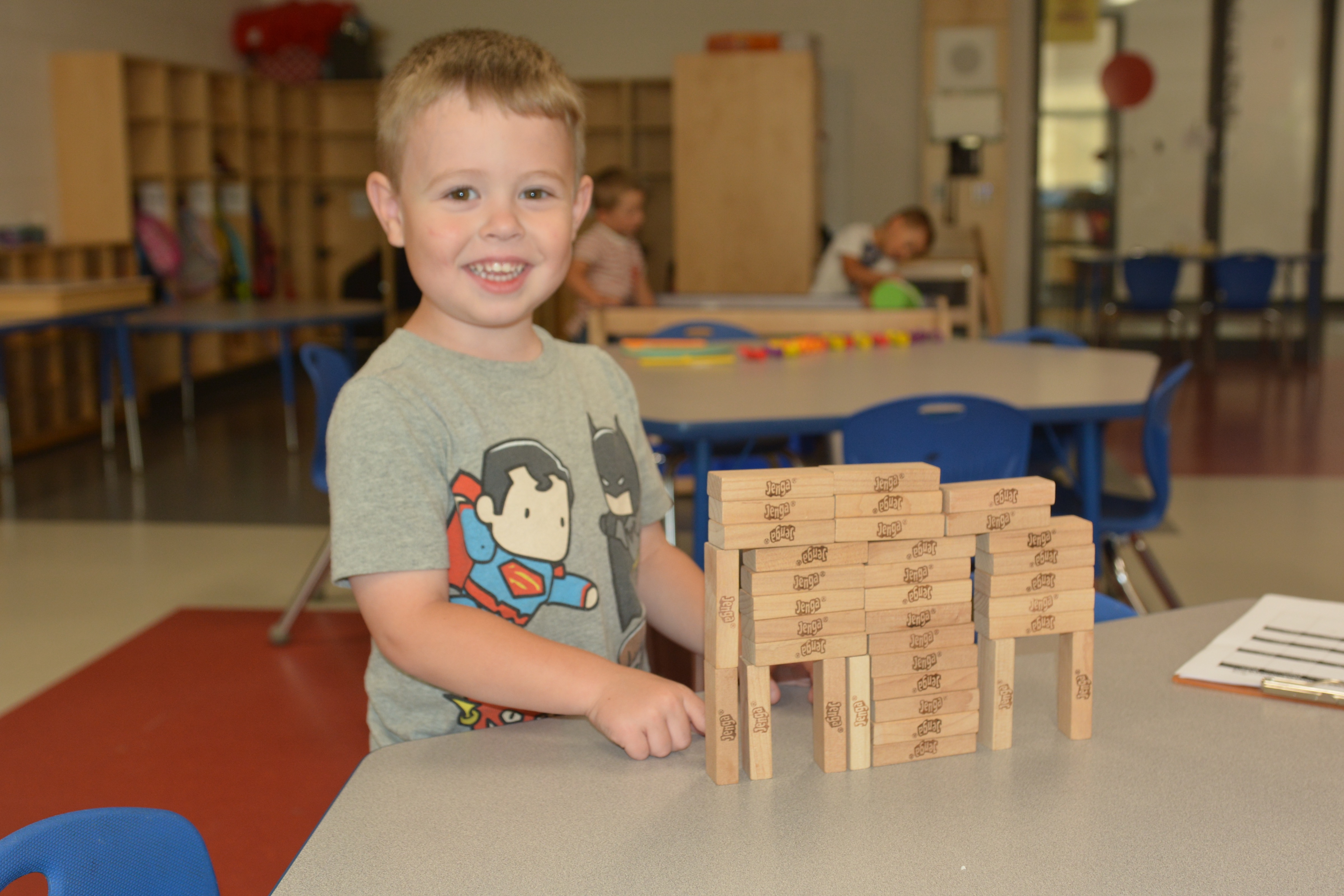 A boy stands with his blocks