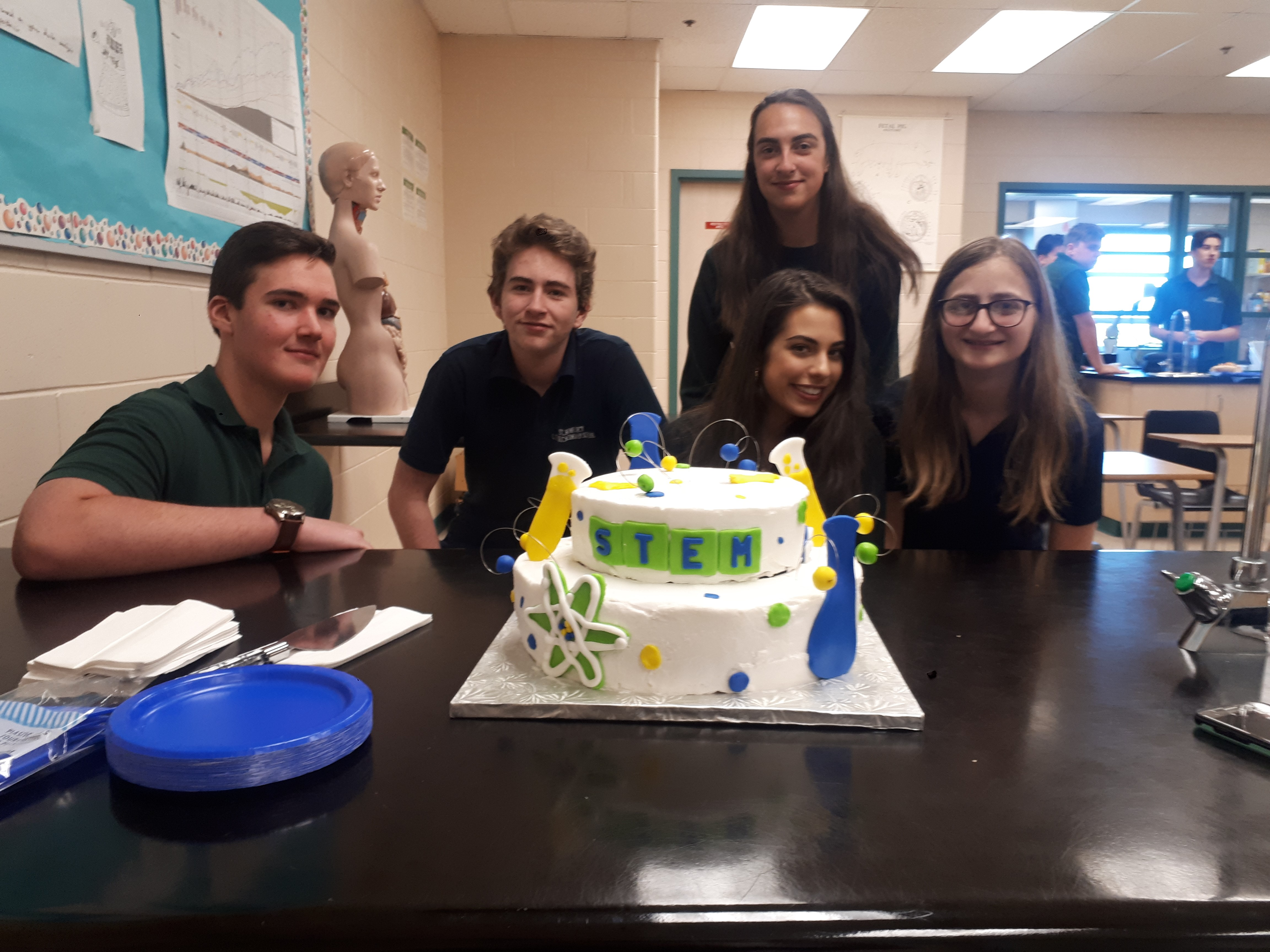 Noah Forteski, Ethan Hodge, Adriana Cimino and Livea Donato with Erika Poirier in the background pose with the STEM Club cake in foreground
