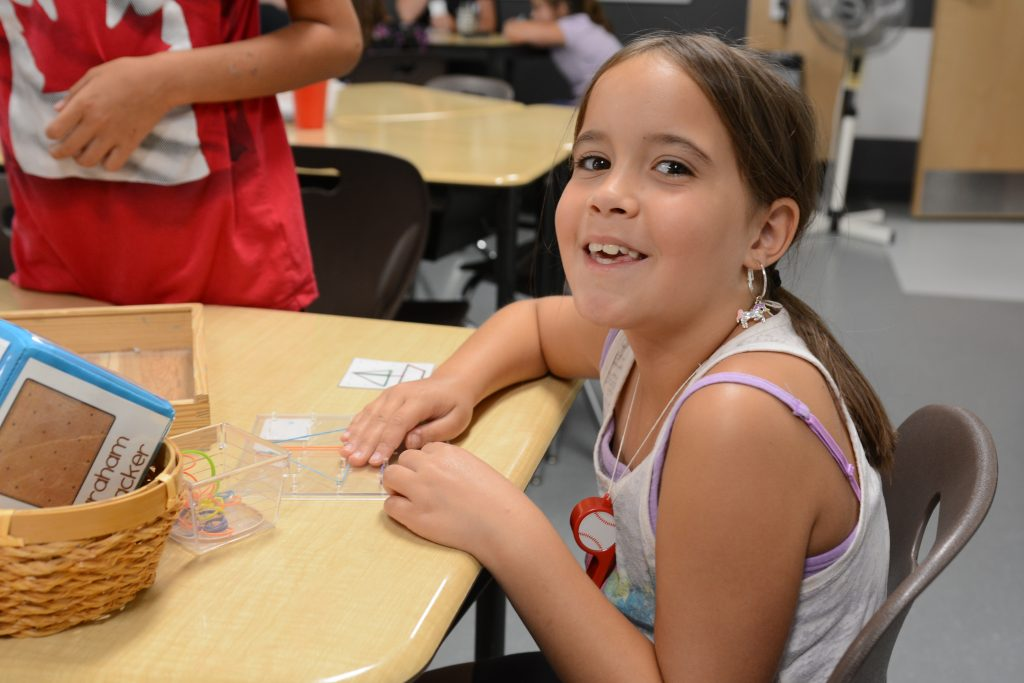 A student is all smiles as she completes a shape building activity with elastics.