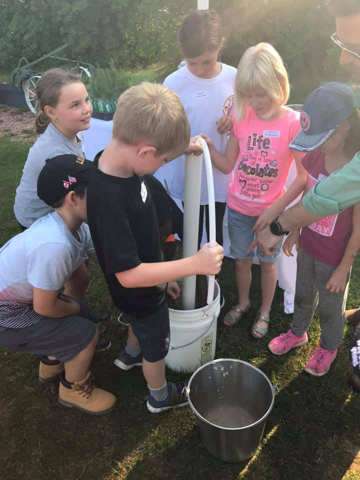 A group of students source water from a bucket.