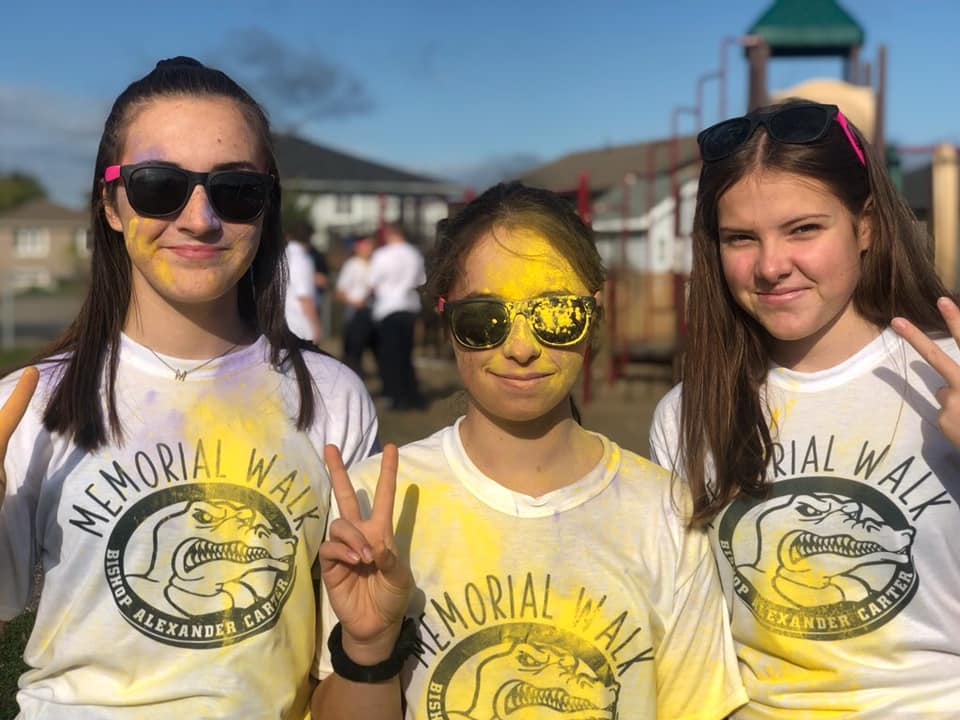 Three girls stand and smile in their Memorial Walk T-shirts