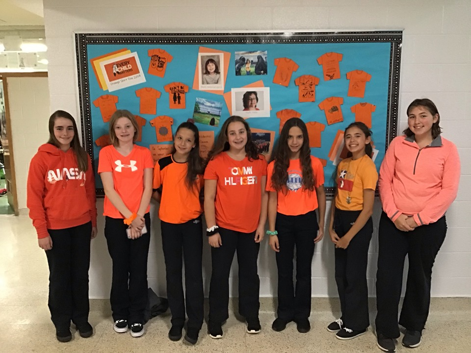A group of girls wear their orange shirts and stand in a line.