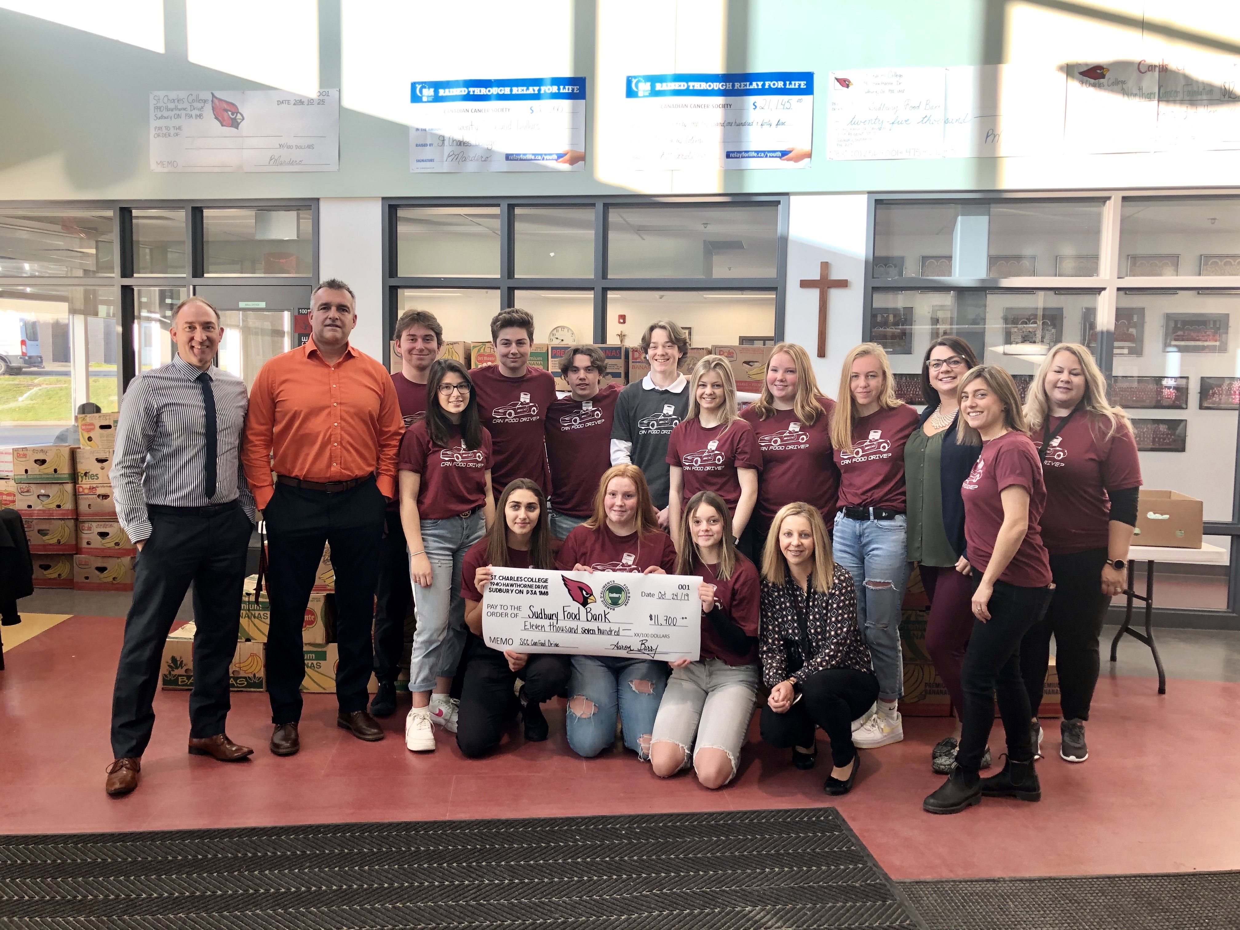 Staff and students gather together with a giant cheque for over $11,000