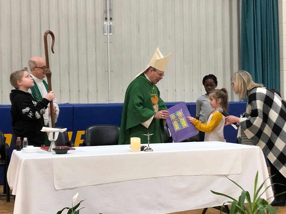 Bishop recieves card from a student.