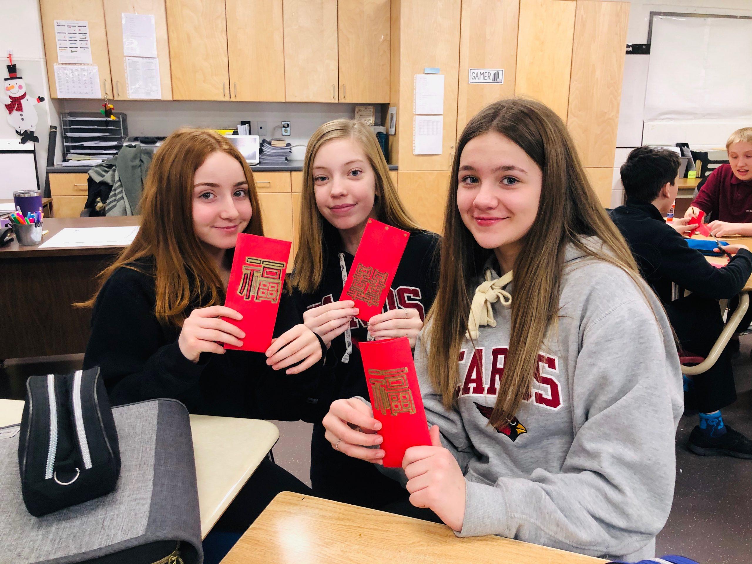 Girls hold up red envelopes