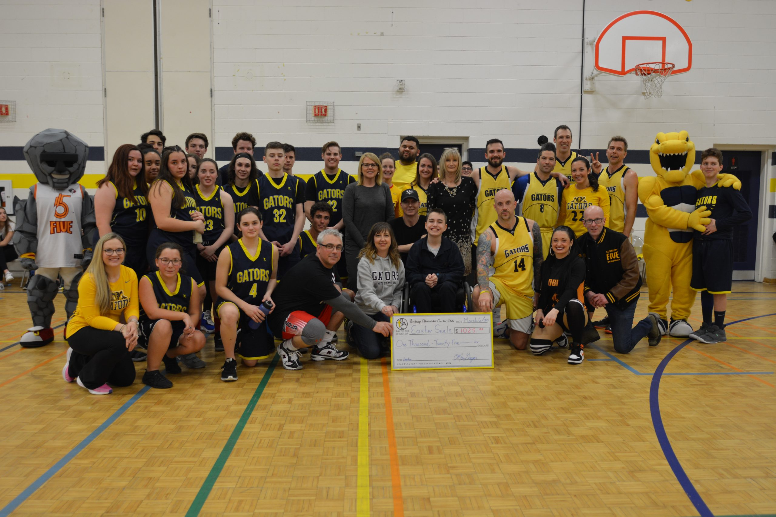 Group stands together with giant cheque