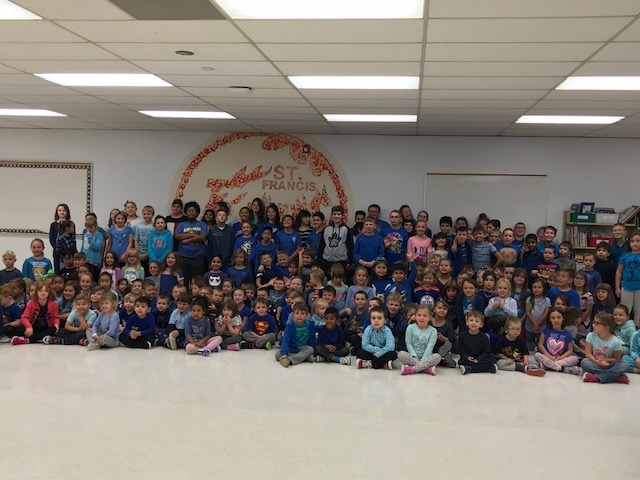 Group of students and staff members from St. Francis school dressed in blue sit smiling.