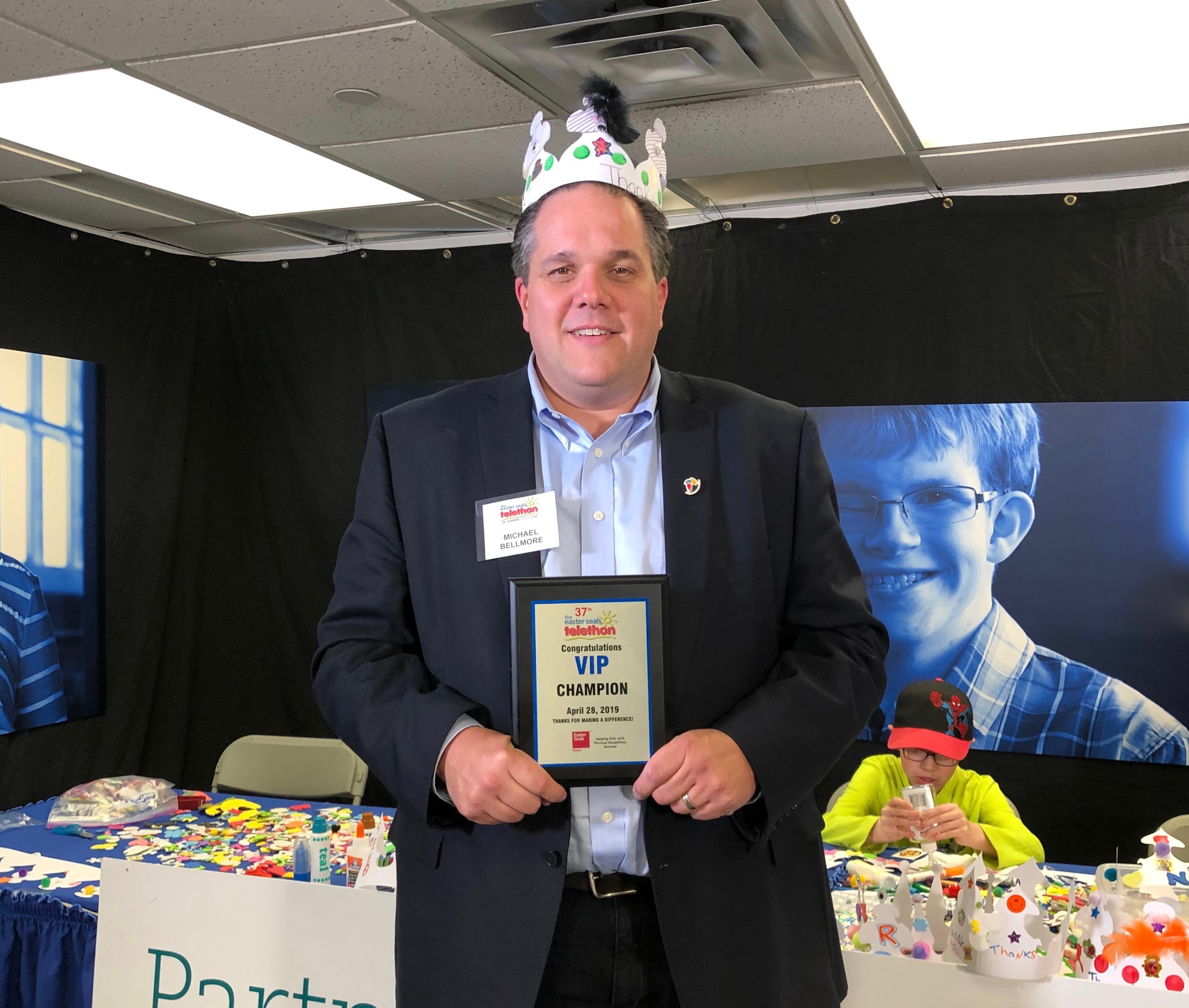 Board Chair Michael Bellmore stands with his VIP Champion Plaque