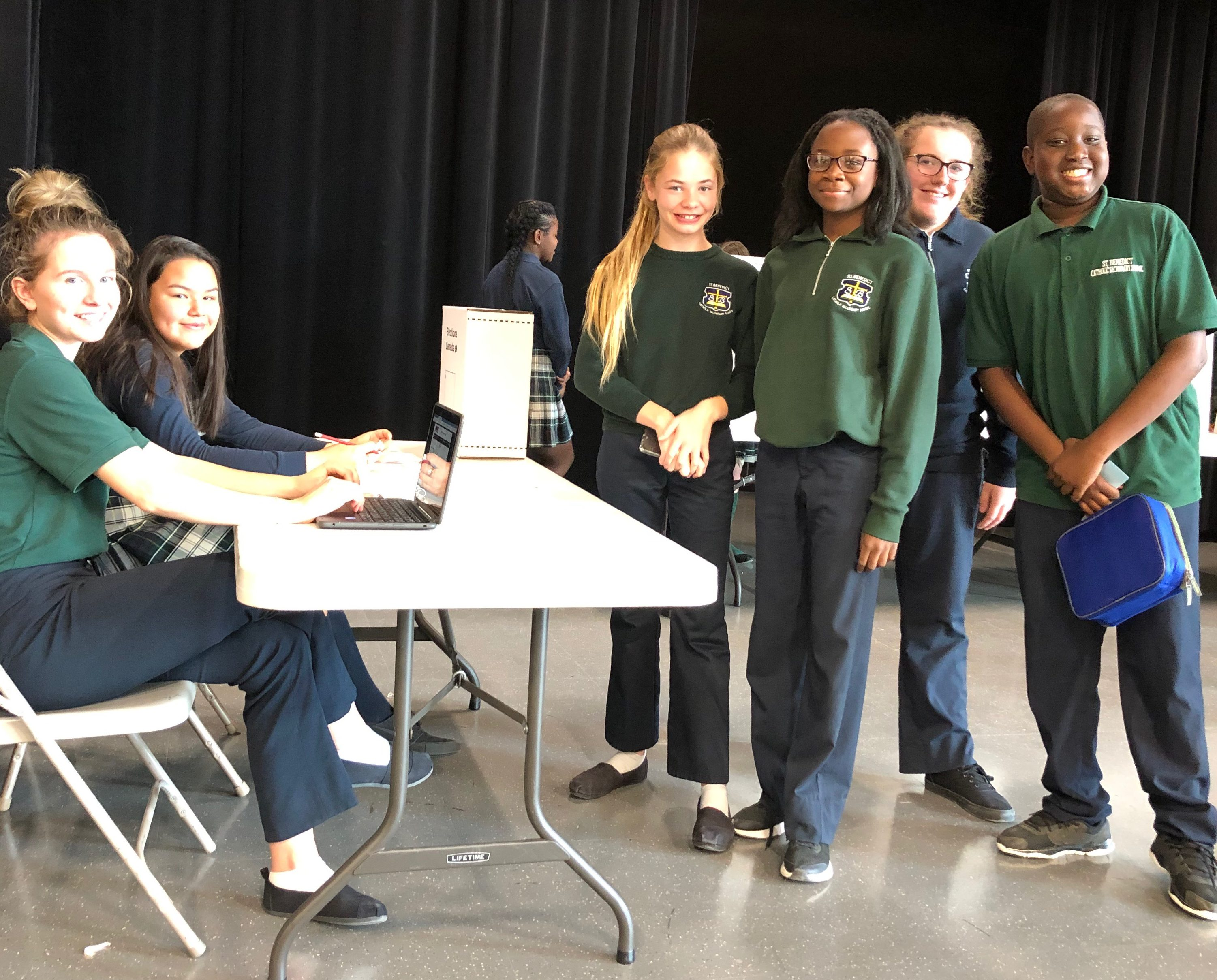 A group of students stand in line by the election booth.