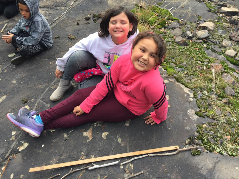 Two girls lay next to a stick used for measurement.