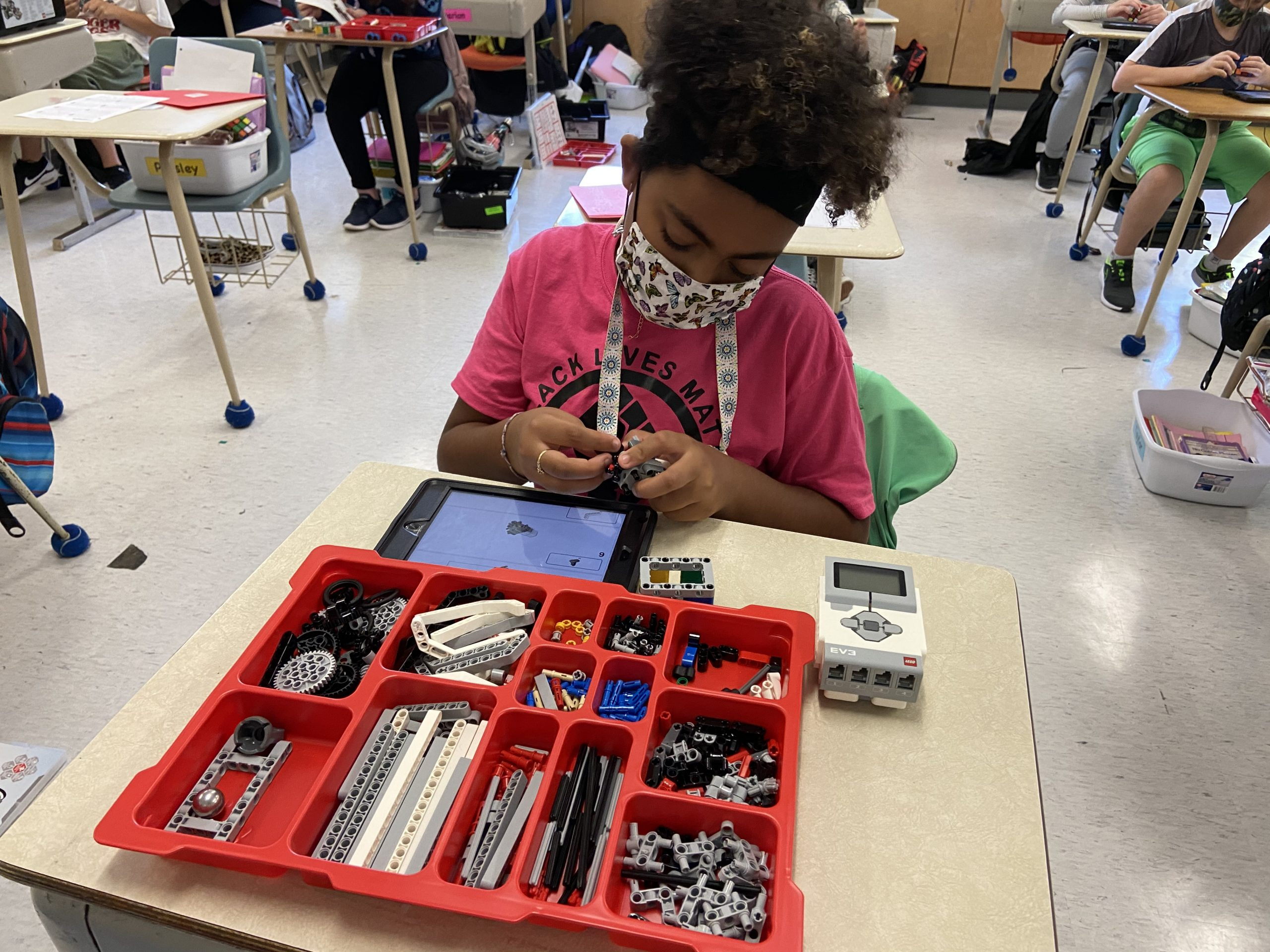 A girl works with her robot kit.
